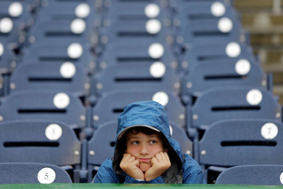 Bennett Cheer, 12, Williston, Vt., sits in the rain before a baseball game between the Washington Nationals and the New York Mets at Nationals Park Thursday, June 6, 2013, in Washington. (AP Photo/Alex Brandon) / AP