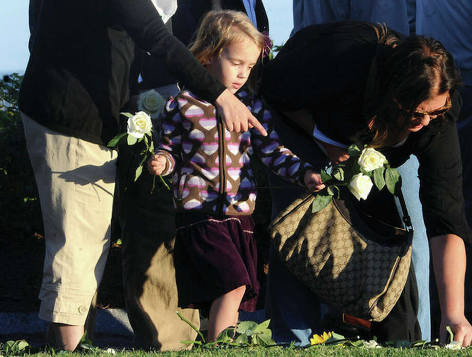 Lainey Grume, 4, puts flowers down for her uncle Derek Statkericus who died on Sept. 11, 2001, at the World Trade Center in NYC. The annual memorial service was held at Sherwood Island Park in Westport.