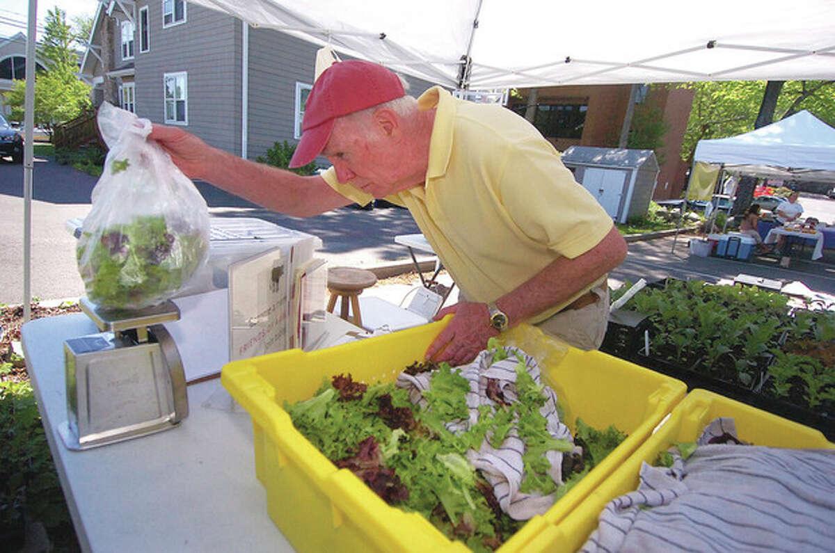 File photo/Alex von Kleydorff. Dan Riley weighs some fresh-cut lettuce from Ambler Farm at a past Wilton Farmers' Market.