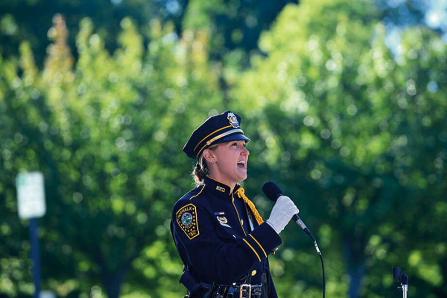 Lt. Christa LePak sings the national anthem while city officials, police and firefighters honor those lost on September 11th 2001 during a brief flag raising ceremony Tuesday. Hour photo / Erik Trautmann / (C)2012, The Hour Newspapers, all rights reserved
