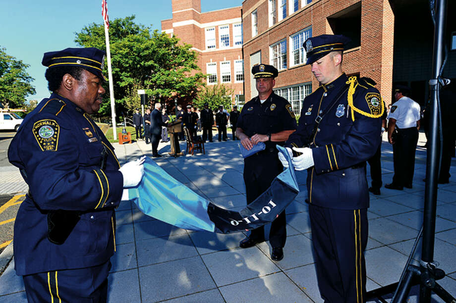 The Norwalk Police Pepartment honor guard prepares to raise the flag while city officials, police and firefighters honor those lost on September 11th 2001 during a brief flag raising ceremony Tuesday. Hour photo / Erik Trautmann / (C)2012, The Hour Newspapers, all rights reserved