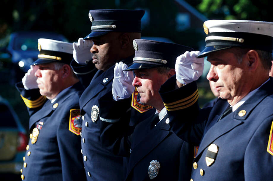 City officials, police and firefighters honor those lost on September 11th 2001 during a brief flag raising ceremony Tuesday. Hour photo / Erik Trautmann / (C)2012, The Hour Newspapers, all rights reserved