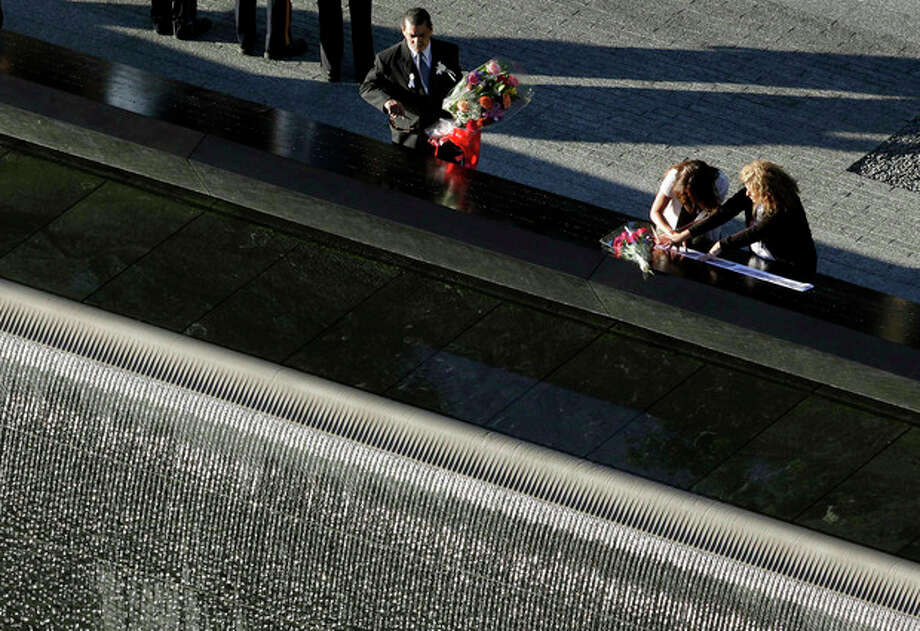 A man paces a bouquet of flowers at a reflecting pool during a ceremony at the National September 11 Memorial, Tuesday, Sept. 11, 2012 in New York. As in past years, thousands are expected to gather at the World Trade Center site in New York, the Pentagon and Shanksville, Pennsylvania, to read the names of nearly 3,000 victims killed in the worst terror attack in U.S. history. (AP Photo/Mark Lennihan) / AP