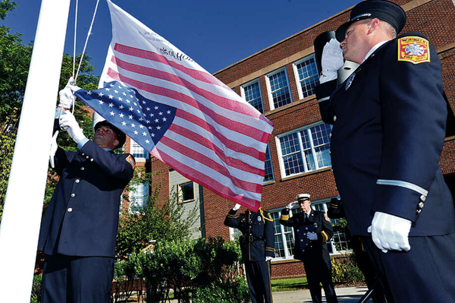 The Norwalk Fire Department honor guard raises the flag while city officials, police and firefighters honor those lost on September 11th 2001 during a brief flag raising ceremony Tuesday. Hour photo / Erik Trautmann / (C)2012, The Hour Newspapers, all rights reserved