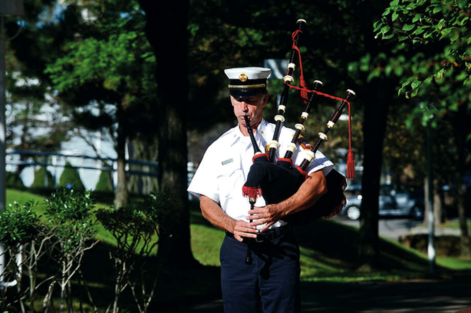 Assiatnt Chief Ed Prescott plays the bag pipes while city officials, police and firefighters honor those lost on September 11th 2001 during a brief flag raising ceremony Tuesday. Hour photo / Erik Trautmann / (C)2012, The Hour Newspapers, all rights reserved