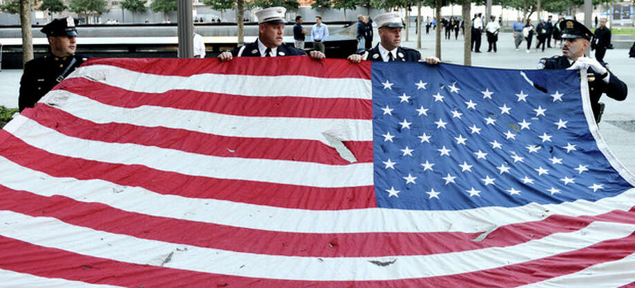 Police officers of the Port Authority of New York and New Jersey, carry an American flag that flew over at the World Trade Center towers, during the 11th anniversary ceremonies at the site of the World Trade Center, in New York, Tuesday Sept. 11, 2012. (AP Photo/Justin Lane, Pool, EPA) / Pool EPA