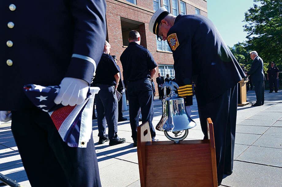 Norwalk Fire Department Assistant Chief Lawrence Reilly tolls the bell for those lost on 911 in the city's flag raising remembrance ceremony Tuesday. Hour photo / Erik Trautmann / (C)2012, The Hour Newspapers, all rights reserved