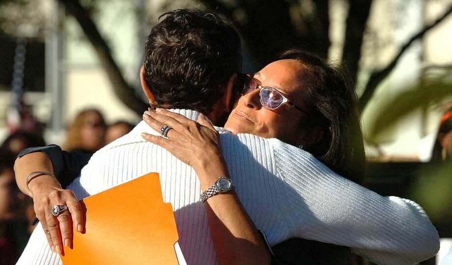 Hour Photo/ Alex von Kleydorff. Lynne McGuinn hugs West Rocks Principal Lynne Moore after talking to the school about her husband who was killed on 9/11