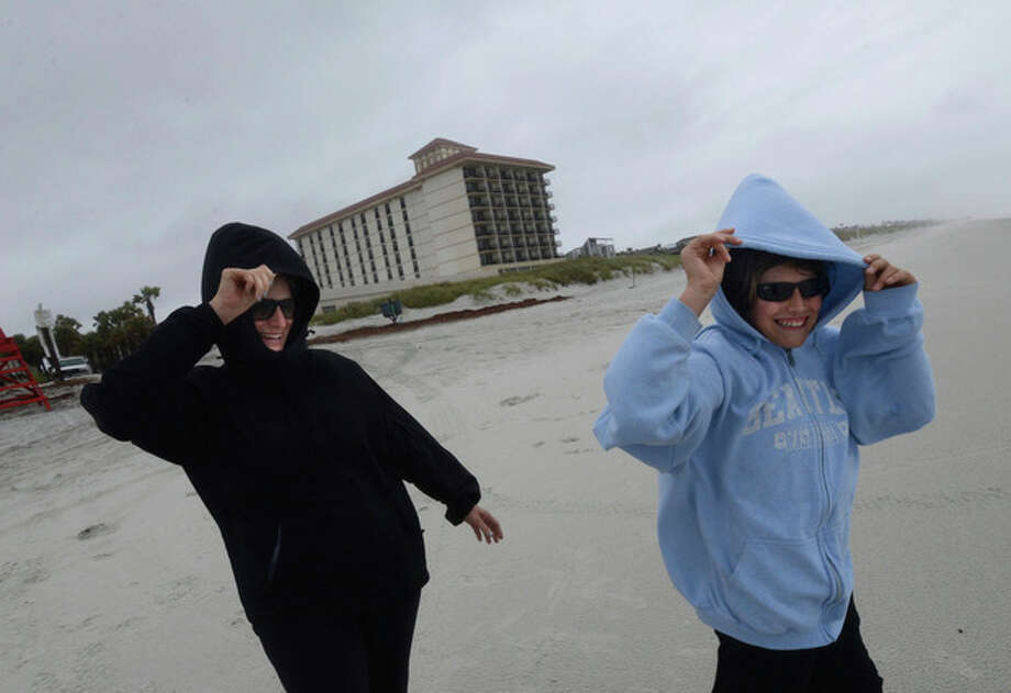"Beach residents Sherry Fix, left, and her son James, 11, hold their hoods as they venture out on Neptune Beach, Fla. to check out the waves Thursday, June 6, 2013. ""This is what you are supposed to do on the last day of school, come to the beach,"" Sherry said. Tropical Storm Andrea, the first named storm of the Atlantic season, hammered Florida with rain, heavy winds, and tornadoes Thursday as it moved toward the coast of Georgia and the Carolinas, promising sloppy commutes and waterlogged vacation getaways through the beginning of the weekend. (AP Photo/The Florida Times-Union, Bob Mack) / The Florida Times-Union"