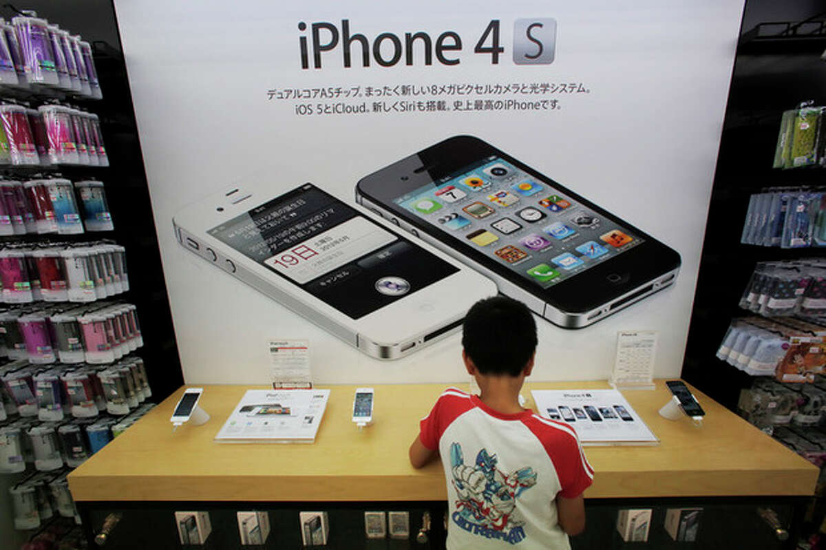 FILE-In this Friday, Aug. 31, 2012 file photo, a boy checks an iPhone at an Apple booth at an electronic store in Tokyo. Millions of people will likely buy new iPhones after Apple's expected announcement of a new model on Wednesday, Sept. 12, 2012. The new phones would join some 244 million iPhones already sold since the first one launched in 2007. Some have been lost, some stolen and some are still in use. But it's fair to say that millions of iPhones are languishing in desk drawers or gathering dust. (AP Photo/Itsuo Inouye, File)