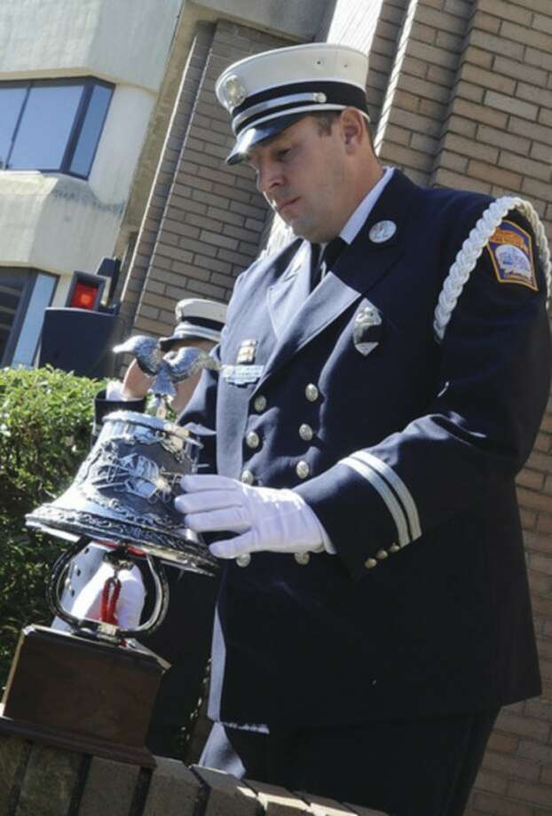 Captain Chris Ward sounds the bell at the Stamford Fire & Rescue Department and Stamford Professional Fire Fighters Association's 9/11 memorial observation Tuesday. photo/Matthew Vinci