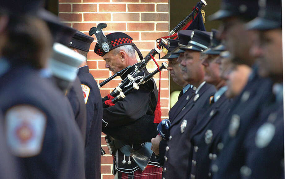 Hour Photo/ Alex von Kleydorff. Wilton Fire Dept Bagpiper Ralph Nathanson bows his head with others during a moment of silence at Wilton's 9/11 anniversary program / 2012 The Hour Newspapers