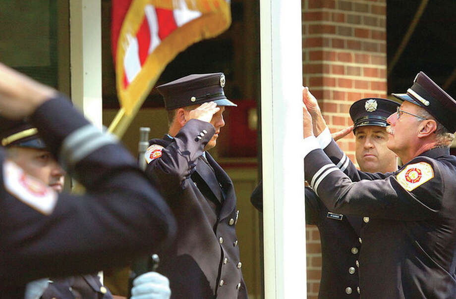 Hour Photo/ Alex von Kleydorff. Wilton Fire departments Color Guard raises the flag to half staff at Wilton's 9/11 anniversary program / 2012 The Hour Newspapers