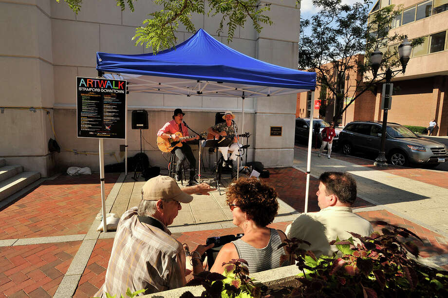 Listeners watch Dan Swartz, left, and Seth Lefferts perform in Kiwanis Park during the annual Artwalk in downtown Stamford, Conn., on Friday, June 26, 2015. The Artwalk continues on Saturday from 2-6 p.m. throughout downtown. For more information, go to http://stamford-downtown.com. Photo: Jason Rearick / Hearst Connecticut Media / Stamford Advocate
