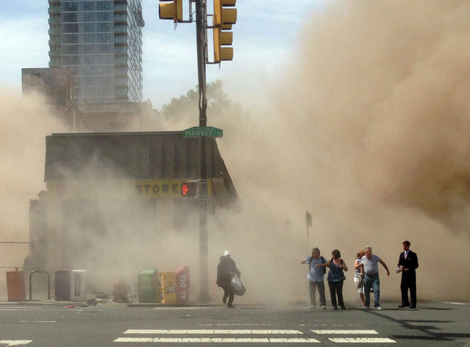 In this photo provided by Jordan McLaughlin, a dust cloud rises as people run from the scene of a building collapse on the edge of downtown Philadelphia on Wednesday, June 5, 2013. Buoyed by the discovery of a woman buried in rubble nearly 13 hours later, rescue workers on Thursday were digging through the debris from the building collapse that killed six people a day earlier. (AP Photo/Jordan McLaughlin) / Jordan McLaughlin