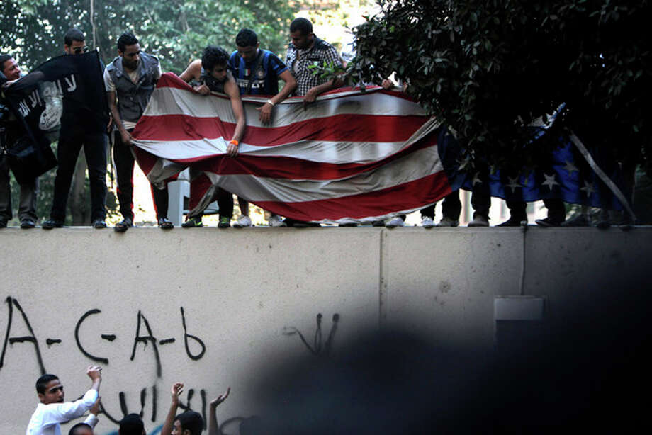 Protesters carry an American flag pulled down from the U.S. embassy in Cairo, Egypt, Tuesday, Sept. 11, 2012. Egyptian protesters, largely ultra conservative Islamists, have climbed the walls of the U.S. embassy in Cairo, went into the courtyard and brought down the flag, replacing it with a black flag with Islamic inscription, in protest of a film deemed offensive of Islam. (AP Photo/Nasser Nasser) / AP