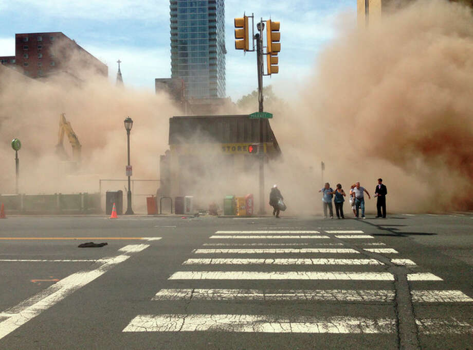 AP10ThingsToSee - A dust cloud rises as people run from the scene of a building collapse on the edge of downtown Philadelphia on Wednesday, June 5, 2013. At least six people were killed and 14 inured after the structure collapsed. (AP Photo/Jordan McLaughlin, File) / Jordan McLaughlin