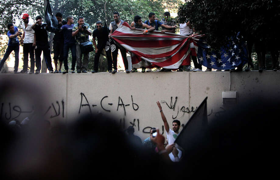 Egyptian protesters standing on the sidewall of the U.S. embassy move down an American flag pulled down from the embassy in Cairo, Egypt, Tuesday, Sept. 11, 2012. Egyptian protesters, largely ultra conservative Islamists, have climbed the walls of the U.S. embassy in Cairo, went into the courtyard and brought down the flag, replacing it with a black flag with Islamic inscription, in protest of a film deemed offensive of Islam. (AP Photo/Nasser Nasser) / AP