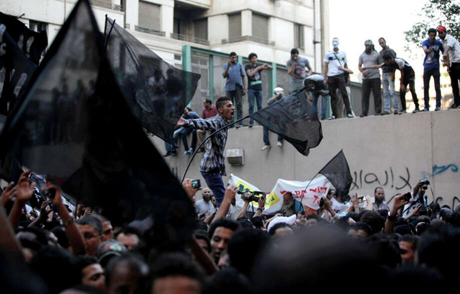"Egyptian protesters climb the walls of the U.S. embassy while others chant anti U.S. slogans during a protest in Cairo, Egypt, Tuesday, Sept. 11, 2012. Egyptian protesters, largely ultra conservative Islamists, have climbed the walls of the U.S. embassy in Cairo, went into the courtyard and brought down the flag, replacing it with a black flag with Islamic inscription, in protest of a film deemed offensive of Islam. Arabic graffiti reads ""Their is only one God."" (AP Photo/Nasser Nasser) / AP"