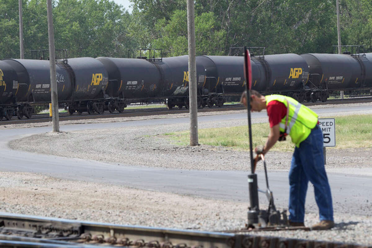 In this Aug. 8, 2012 photo, a worker is seen as DOT-111 and AAR-211 class rail tankers pass by at the Union Pacific rail yard in Council Bluffs, Iowa. For two decades, DOT-111 rail tankers have been allowed to haul hazardous liquids from coast to coast even though transportation officials were aware of a dangerous design flaw that almost guarantees the car will tear open in an accident. The rail and chemical industries have committed to a safer design for new tankers, but they do not want to modify tens of thousands of existing cars. That?'s despite a spike in the number of accidents. (AP Photo/Nati Harnik)