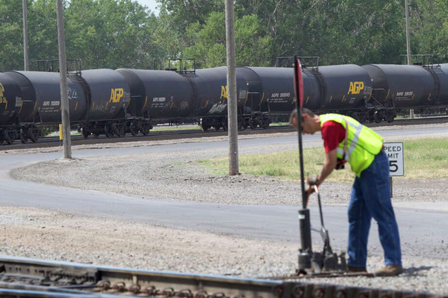 In this Aug. 8, 2012 photo, a worker is seen as DOT-111 and AAR-211 class rail tankers pass by at the Union Pacific rail yard in Council Bluffs, Iowa. For two decades, DOT-111 rail tankers have been allowed to haul hazardous liquids from coast to coast even though transportation officials were aware of a dangerous design flaw that almost guarantees the car will tear open in an accident. The rail and chemical industries have committed to a safer design for new tankers, but they do not want to modify tens of thousands of existing cars. That's despite a spike in the number of accidents. (AP Photo/Nati Harnik) / AP
