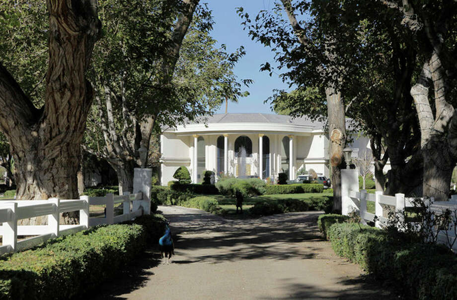 """FILE - In this Friday, Nov. 12, 2010, file photo Wayne Newton's home is framed at the end of a tree-lined lane on a 52-acre estate in Las Vegas. Newton is moving out of this sprawling estate of 45 years. The crooner's family members and a spokesman confirmed Wednesday June 5, 2013, that the downsizing to another mansion involving Newton, family members and a menagerie of exotic animals is taking place this week. Property records show the move is to a $3 million mansion about a mile from Newton's beloved """"Casa de Shenandoah.""""(AP Photo/Julie Jacobson, file) / AP"""