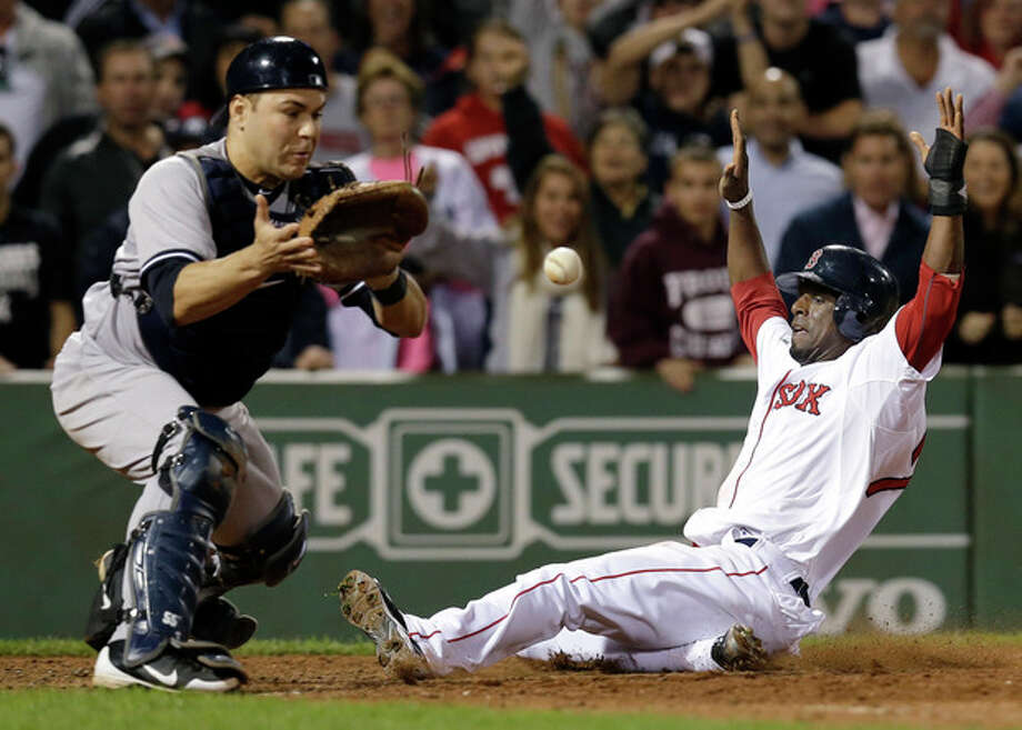 Boston Red Sox's Pedro Ciriaco slides in to score the winning run on a single hit by Jacoby Ellsbury as New York Yankees catcher Russell Martin, left, waits for the late throw during the ninth inning of a baseball game at Fenway Park in Boston, Tuesday, Sept. 11, 2012. The Red Sox won 4-3. (AP Photo/Elise Amendola) / AP