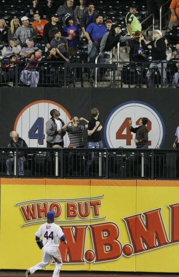 New York Mets left fielder Jason Bay chases a ball hit by Washington Nationals' Tyler Moore to the wall as a fan catches the ball during the seventh inning of a baseball game Tuesday, Sept. 11, 2012, in New York. (AP Photo/Frank Franklin II)