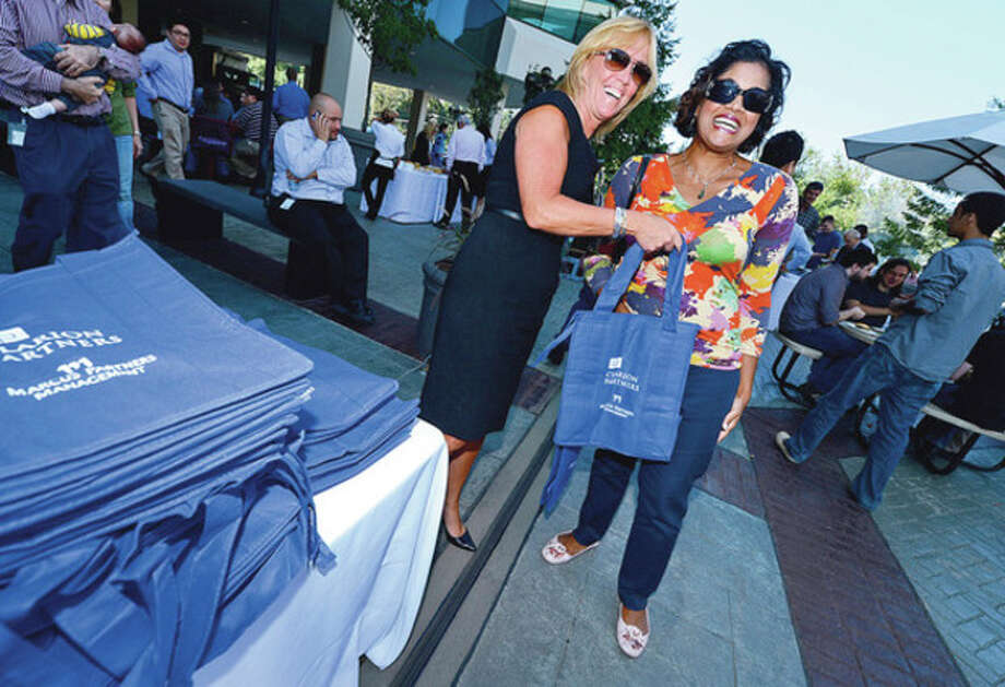 Millward Brown employee Anita Valdes, right, recieves a free tote bag from Marrit 7's Jo Ann McGrath during the Merritt 7 Corporate Park annual Tenant Appreciation Day Wednesday.Hour photo / Erik Trautmann / (C)2012, The Hour Newspapers, all rights reserved