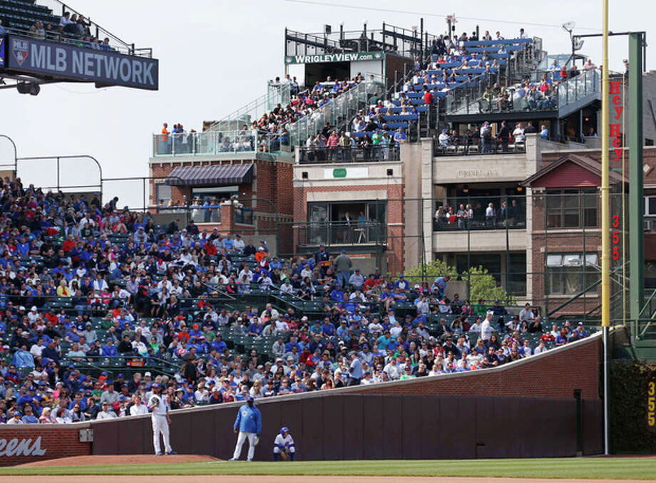 In this May 17, 2013 photo, spectators watch a Chicago Cubs baseball game from several of the rooftop bleachers across the field from Wrigley Field in Chicago. A battle is heating up between the Cubs and rooftop owners across the street from the ballpark as the team proposes renovations, including a Jumbotron in the bleachers, that would block the views and threaten the business those views have created. (AP Photo/Charles Rex Arbogast) / AP