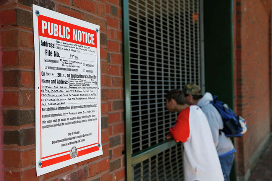 In this May 8, 2013 photo, young fans look inside the concourse at Wrigley Field before a Chicago Cubs baseball game as a public notice regarding planned developments is seen posted outside the ballpark in Chicago. A battle is heating up between the Cubs and rooftop owners as the team proposes renovations, including a Jumbotron in the bleachers, that would block the views and threaten the business those views have created. (AP Photo/Charles Rex Arbogast) / AP