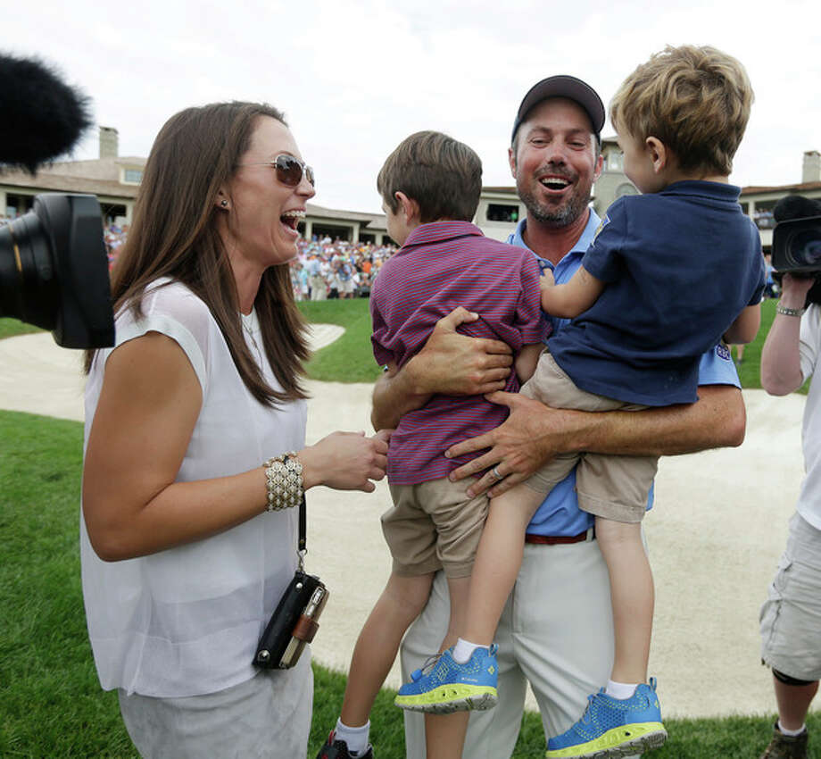Matt Kuchar, second from right, celebrates with his wife, Sybi, left, and children, Cameron, second from left, and Carson after winning the Memorial golf tournament on Sunday, June 2, 2013, in Dublin, Ohio. (AP Photo/Darron Cummings) / AP
