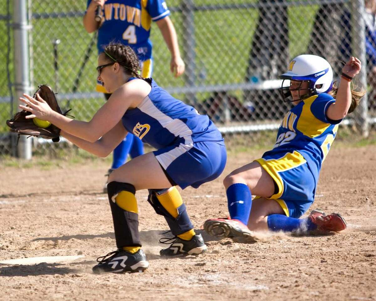 Newtown's Maddy Hauck slides safely across the plate as Brookfield pitcher Kayla Berardi takes the late throw. Hauck, a courtesy runner, scored on a wild pitch Friday at Brookfield High.