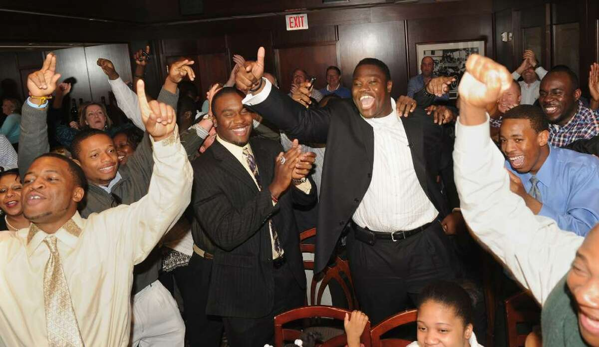 Family and friends rejoice after hearing the news that Vlad Ducasse, back center with arm in air, has been drafted to the New York Jets, during the NFL draft pick gathering at Morton's Steakhouse in downtown Stamford, Conn. on Friday April 23, 2010.