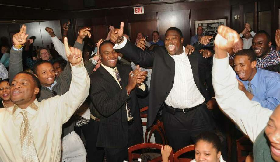 Family and friends rejoice after hearing the news that Vlad Ducasse, back center with arm in air, has been drafted to the New York Jets, during the NFL draft pick gathering at Morton's Steakhouse in downtown Stamford, Conn. on Friday April 23, 2010. Photo: Christian Abraham / Connecticut Post