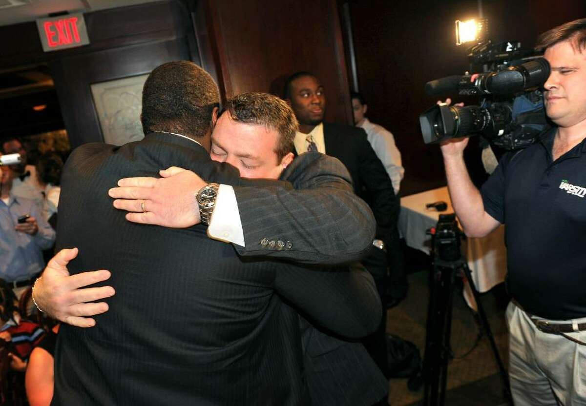 University of Massachusetts football player Vlad Ducasse, facing away from camera, gets a hug from his former coach, Stamford High's Kevin Jones, after learning he will be joining the New York Jets, during the NFL draft pick gathering at Morton's Steakhouse in downtown Stamford, Conn. on Friday April 23, 2010.
