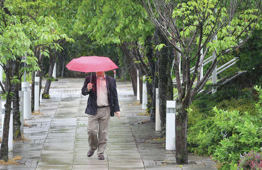 Hour photo / Alex von KleydorffDon't think he is singing or dancingCraig Creller makes his way into City Hall in the rain on Friday aftrenoon. He was lucky to have handy his wife's red umbrella as his was in his car in the shop.