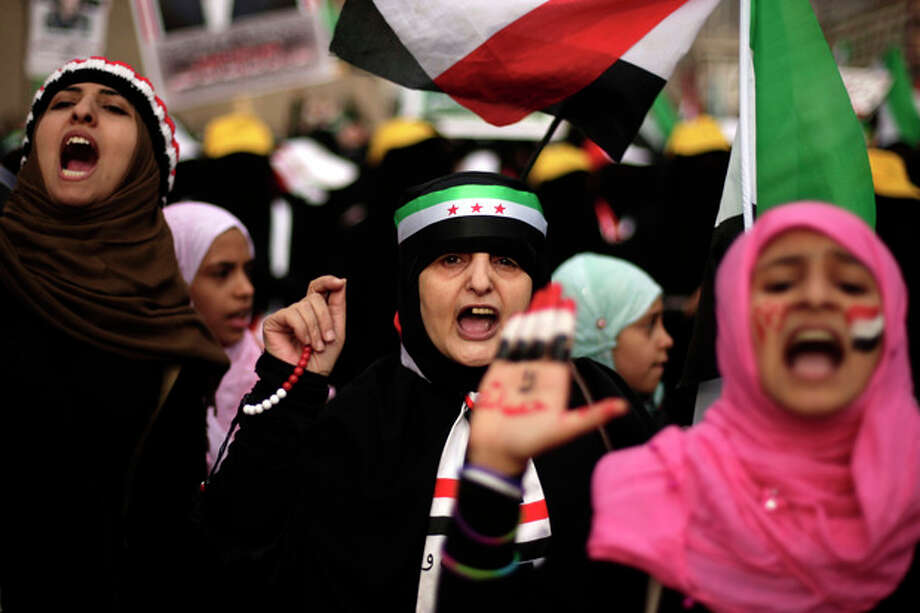 Female protestors, including a woman wearing a headband in the colors of the Syrian revolutionary flag, chant slogans during a demonstration demanding the trial of Yemen's former President Ali Abdullah Saleh in Sanaa, Yemen, Tuesday, Sept. 11, 2012. (AP Photo/Hani Mohammed) / AP