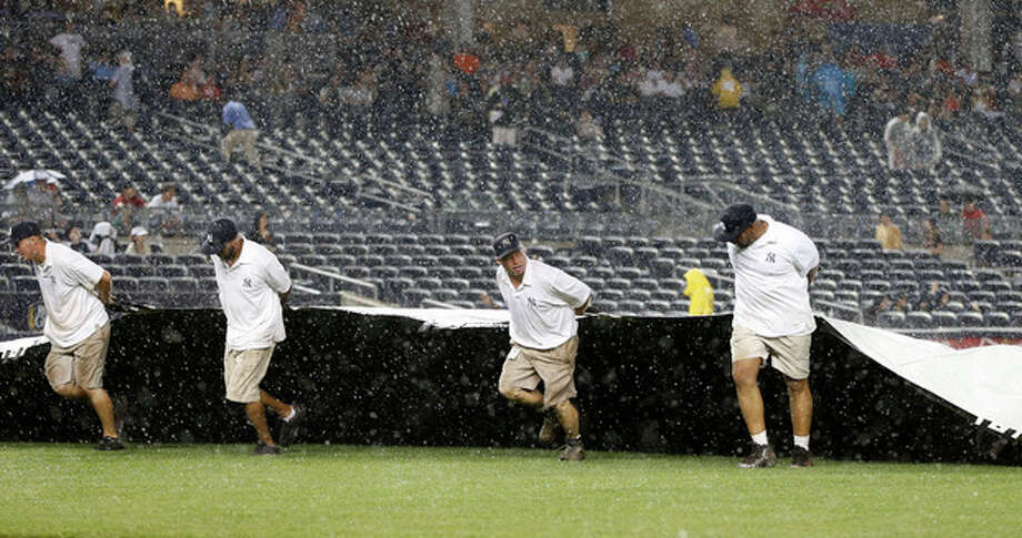 Groundskeepers pull the tarp over the field as rain falls in a baseball game between the New York Yankees and the Boston Red Sox at Yankee Stadium in New York, Sunday, June 2, 2013. (AP Photo/Kathy Willens) / AP