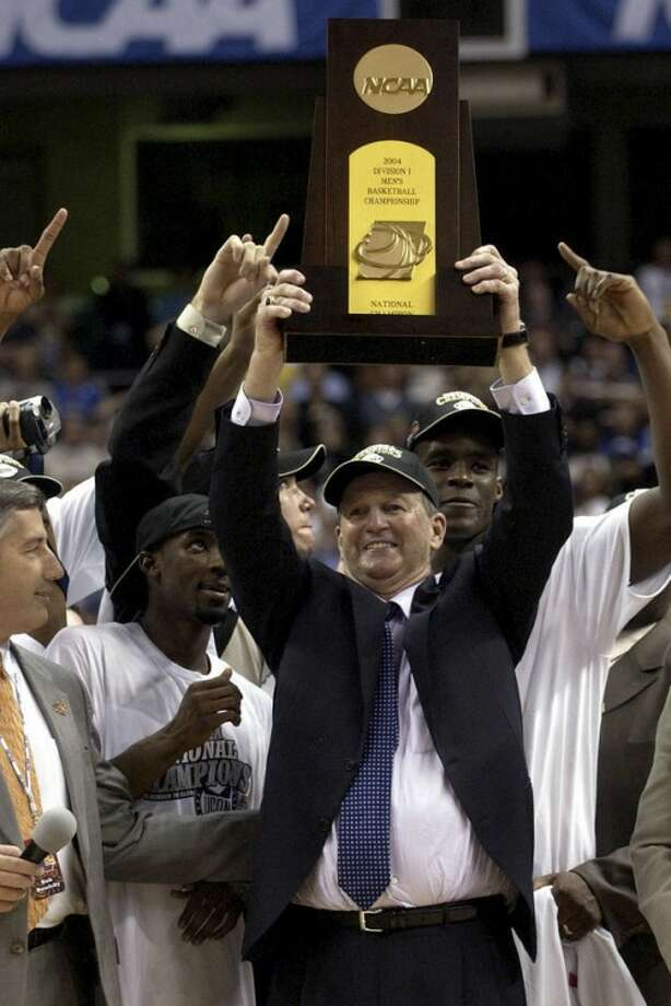 FILE - In this April 5, 2004, file photo, Connecticut head coach Jim Calhoun holds the trophy after his team defeated Georgia Tech 82-73 to win the NCAA Final Four college championship game in San Antonio. Calhoun is expected to announce his retirement on Thursday, Sept. 13, 2012, according to a person familiar with the situation. (AP Photo/Eric Gay, File)