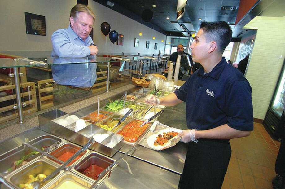 Hour Photo/Alex von Kleydorff. Burittos are made to order at Qdoba Mexican Grill in Norwalk / 2013 The Hour Newspapers