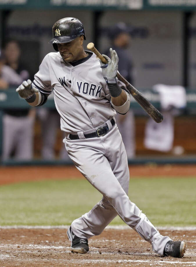 New York Yankees' Robinson Cano is hit with a fifth-inning, bases-loaded pitch by Tampa Bay Rays relief pitcher Cesar Ramos during a baseball game on Friday, May 24, 2013, in St. Petersburg, Fla. Yankees' Lyle Overbay scored on the play.(AP Photo/Chris O'Meara)