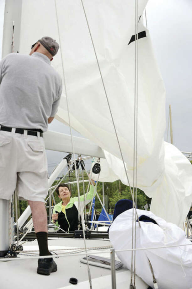 Hour photo / Erik TrautmannGeorge and Jayne Flynn prepare the sailboat at Cove Marina Friday for the upcoming Memorial Day weekend.