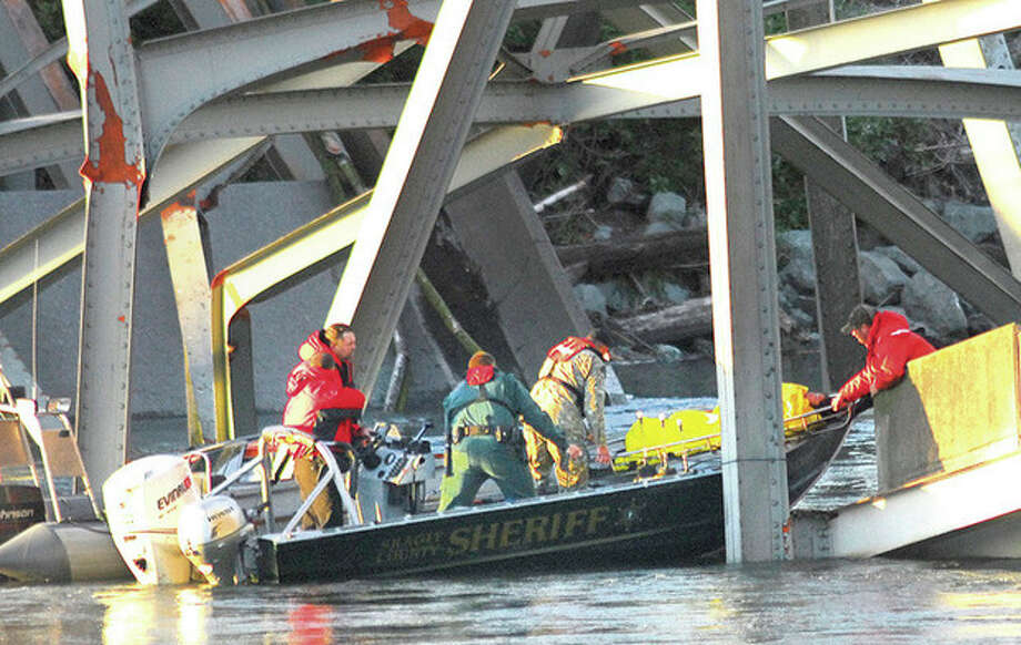 A person is removed from the wreckage of the collapsed Interstate-5 bridge in Mount Vernon, Wash. Thursday May 23, 2012. The Interstate 5 bridge over the Skagit river collapsed north of Seattle Thursday evening, dumping two vehicles into the water and sparking a rescue effort by boats and divers as three injured people were pulled from the chilly waterway. (AP Photo/Skagit Valley Herald, Frank Varga) / (C)2010 {your name}, all rights reserved