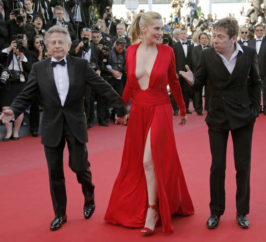 From left, Director Roman Polanski, actors Emmanuelle Seigner and Mathieu Amalric arrive for the screening of the film Venus in Fur at the 66th international film festival, in Cannes, southern France, Saturday, May 25, 2013. (AP Photo/Francois Mori)