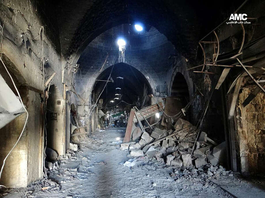 This citizen journalism image provided by Aleppo Media Center AMC which has been authenticated based on its contents and other AP reporting, shows Syrian rebels standing in the middle of a medieval market in Old Aleppo, which has been destroyed by fighting between regime forces and rebels seeking to topple Syrian President Bashar Assad, in Aleppo, Syria, Thursday, May. 23, 2013. Fighting in Qusair continued for a fifth day Thursday, after Syrian opposition leaders urged rebels from elsewhere to converge on the town, which is strategically important to both sides. (AP Photo/Aleppo Media Center AMC)