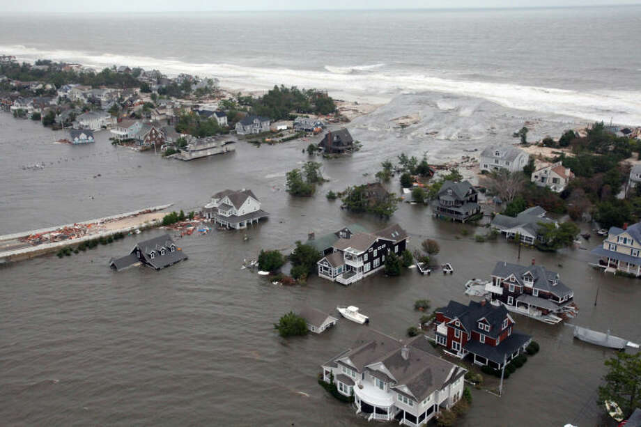 FILE - This Oct. 30, 2012 aerial file photo provided by the U.S. Air Force shows flooding in Mantoloking, N.J., on the New Jersey shoreline caused by Superstorm Sandy. The unprecedented storm surge caused by the storm caused the National Oceanic and Atmospheric Administration to increase the number of storm surge forecasters at the National Hurricane Center starting with the 2013 Atlantic Hurricane season. They will also provide potential storm surge hazards at least 48 hours before the onset of tropical storm or gale-force winds. (AP Photo/U.S. Air Force, Master Sgt. Mark C. Olsen, File)