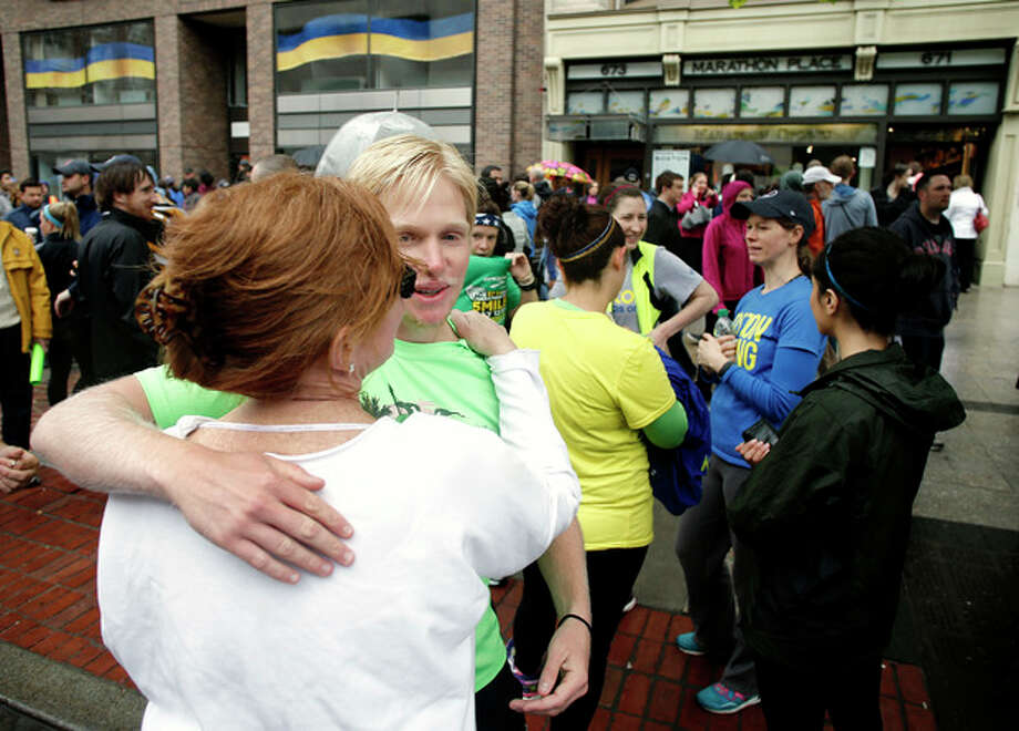 Nick Pelton, of Florida, hugs his mom, Colleen, after watching runners who were unable to finish the Boston Marathon because of the bombings on April 15, cross the finish line on Boylston Street after the city allowed them to finish the last mile of the race, in Boston, Saturday, May 25, 2013. (AP Photo/Winslow Townson) / FR170221 AP