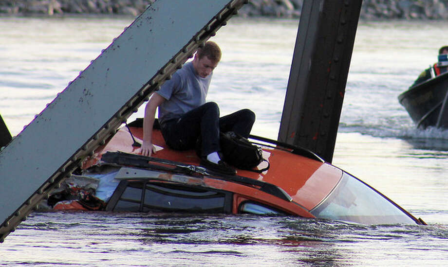 In this photo provided by Francisco Rodriguez, Bryce Kenning sits atop his car that fell into the Skagit River after the collapse of the Interstate 5 bridge there minutes earlier Thursday, May 23, 2013, in Mount Vernon, Wash. (AP Photo/Francisco Rodriguez) / AP