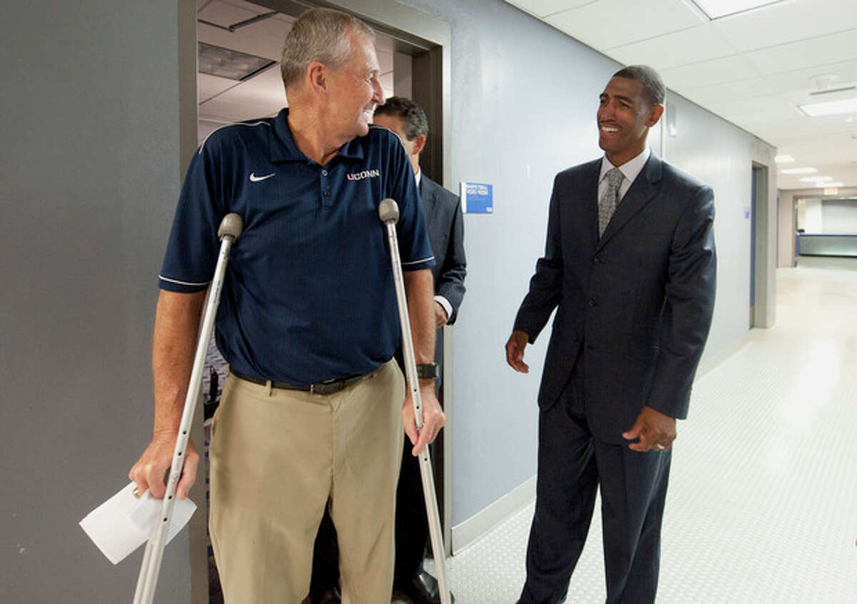 Retired Connecticut head coach Jim Calhoun, left, talks to Kevin Ollie after a news conference announcing Calhoun's retirement, Thursday, Sept. 13, 2012, in Storrs, Conn. Ollie, an assistant coach under Calhoun, will succeed him. (AP Photo/Jessica Hill)